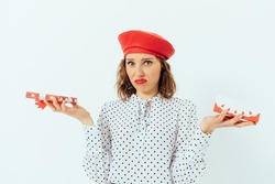 Confused unhappy young woman wearing red beret received wrong present, holding an open gift box and lid looking sadly at camera while standing on white studio background.