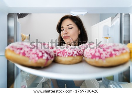 Confused Woman Thinking Looking At Sweets In Fridge Or Refrigerator Foto d'archivio ©