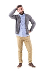 Confused young bearded stylish casual man with hand in hair looking at camera. Full body length portrait isolated on white studio background.