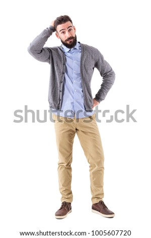 Confused young bearded stylish casual man with hand in hair looking at camera. Full body length portrait isolated on white studio background. #1005607720