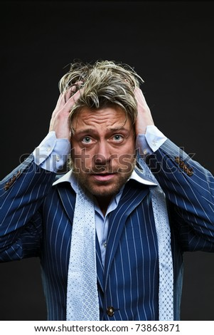 Confused young business man in blue striped suit. Thinking. Lost. Crisis. Panic. Scared. Short blond hair. Studio portrait. Black background.