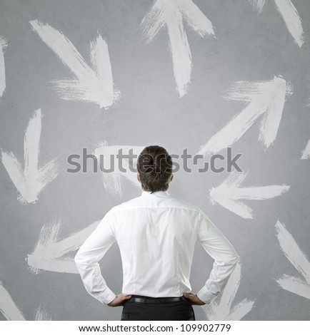 Confused, young businessman looking at many arrows pointed in different directions