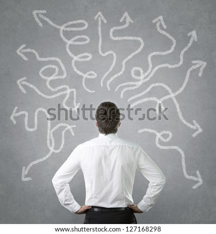 Confused, young businessman looking at many twisted arrows on the concrete wall