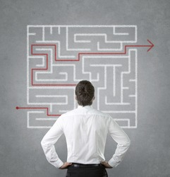 Confused, young businessman looking at the red arrow through the labyrinth