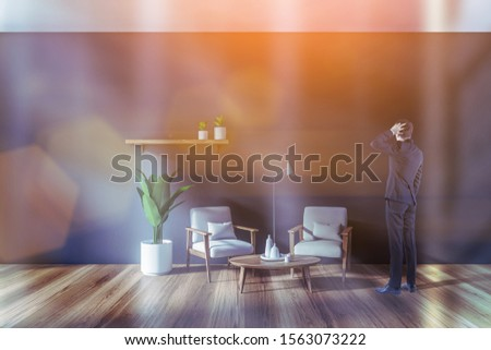 Confused young businessman standing in modern living room with gray walls, wooden floor, two white armchairs near coffee table and shelf with plants. Toned image #1563073222