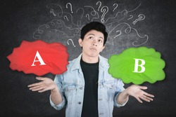 Confused young man choosing option A or option B with chaotic symbol background