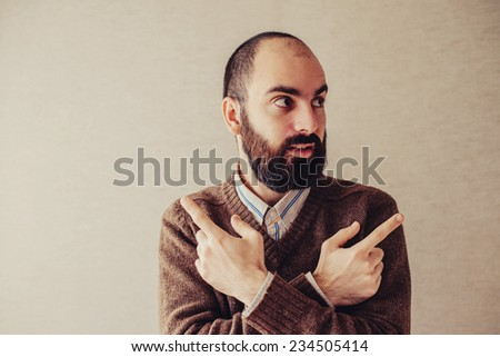 confused young man pointing in two different directions