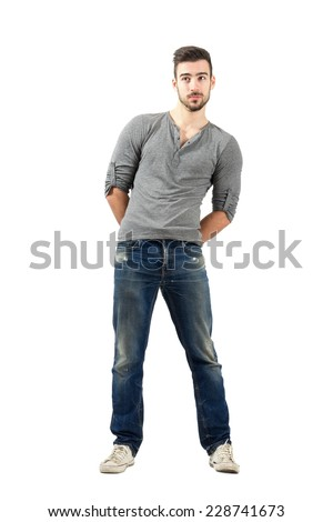Confused young man with hand clasped on his back. Full body length isolated over white background.