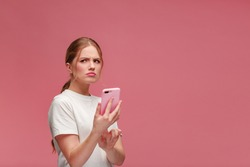 Confused young redhead woman holding pink smartphone.Embarassed woman has problem with broken not working mobile phone.Receiving bad news or email,spam message.Young people working with mobile devices.