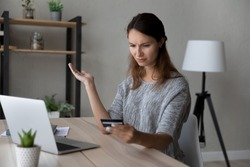 Confused young woman holding credit card in hands, stressed by financial payment mistake, blocked e-banking account or low quality money transfer service, feeling insecure shopping online at home.