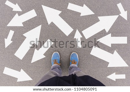 Confusing direction arrows on asphalt ground, feet and shoes on floor, personal orientation concept