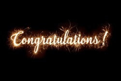 Congratulations banner text in dazzling sparkler effect on dark background