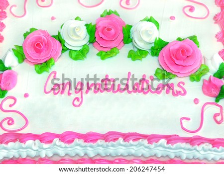 Congratulations in iced writing decorates frosted white cake.  Roses in pink and white sit in swirls amid green leaves.  Mounds of white frosting leaves room for personalization. #206247454