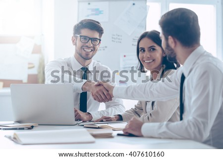 Congratulations! Two handsome man shaking hands with smile while sitting at the office table with their beautiful coworker