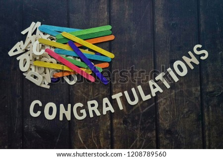 CONGRATULATIONS word by wood letters on wood background.  #1208789560