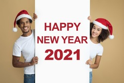 Congratulatory billboard with inscription, Happy New Year 2021. Cheerful african american couple in Santa hats and white t-shirt hold banner, look at camera isolated on light background, studio shot