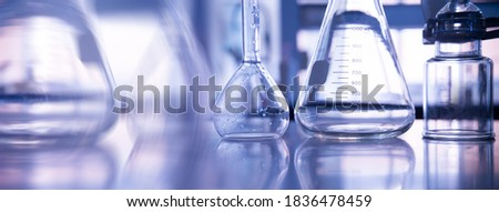 conical and volumetric glass flask with science equipment in chemistry laboratory banner background