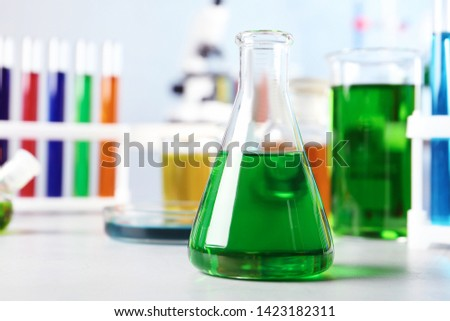 Conical flask and other glassware on table in chemistry laboratory. Space for text #1423182311