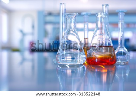conical flask glassware with orange solution in chemical science laboratory in school or university technology background