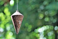 Conical iron, also known as  plummet, rusted, tied with a lanyard hanging from the top and a green bokeh background.