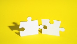 Connect couple puzzle piece on yellow background. Symbol of association and connection, business strategy, completing, team support and help concept. Two wooden puzzles stand almost together. Artwork
