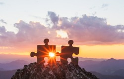 connect couple puzzle piece with sunset background. empty copy space. Jigsaw wooden puzzle against sun. one part of whole. symbol of association and connection. business strategy.