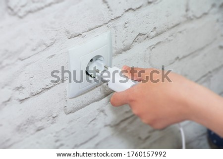 connect the charger to a wall outlet. Save energy-unplug the charger. Foto stock ©
