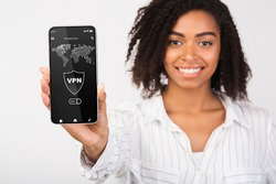 Connect to VPN. Smiling african american woman holding and showing her smartphone with virtual private network application connected to local network over the internet. Information and cyber security