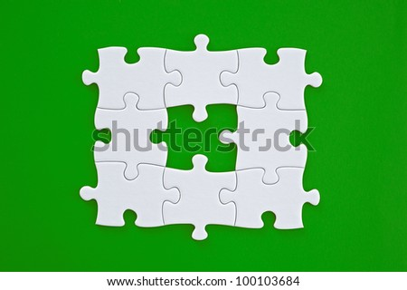 Connected blank puzzle pieces isolated on a green background.