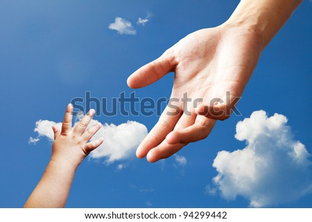Connecting between adult hand and baby hand on sky