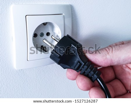 Connecting black electrical power plug with a hand inside a white plastic power socket on a white wall Сток-фото ©