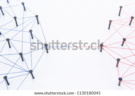 Connecting networks concept - two network connected with yarn red and blue on white paper. Simulator connection social media, internet, people communication #1130180045