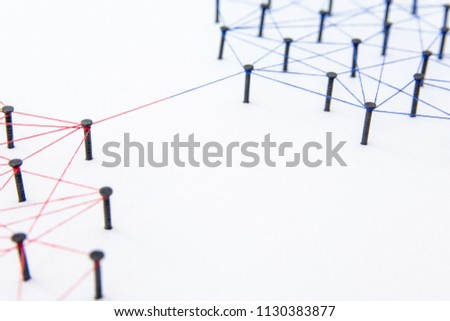 Connecting networks concept - two network connected with yarn red and blue on white paper. Simulator connection social media, internet, people communication #1130383877