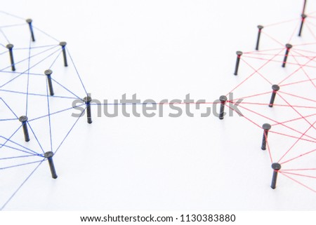 Connecting networks concept - two network connected with yarn red and blue on white paper. Simulator connection social media, internet, people communication #1130383880