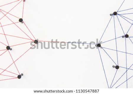 Connecting networks concept - two network connected with yarn red and blue on white paper. Simulator connection social media, internet, people communication #1130547887
