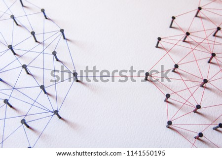 Connecting networks concept - two network connected with yarn red and blue on white paper. Simulator connection social media, internet, people communication #1141550195