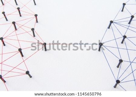 Connecting networks concept - two network connected with yarn red and blue on white paper. Simulator connection social media, internet, people communication #1145650796