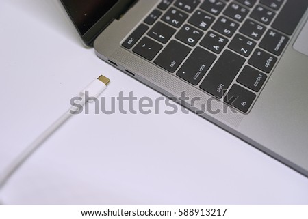 Connecting USB type C cable to laptop computer on white background #588913217