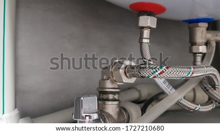 Connection of water supply, hot and cold water to the boiler. Hose for hot and cold water in the bathroom. Plumbing connections for a domestic electric water heater.