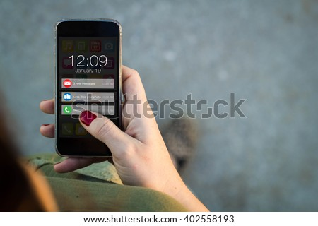 connectivity concept: Top view of woman walking in the street using her mobile phone with notifications on screen. All screen graphics are made up.