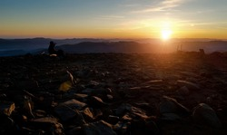 Conquering a mountain peak by a traveler at sunrise, silhouette