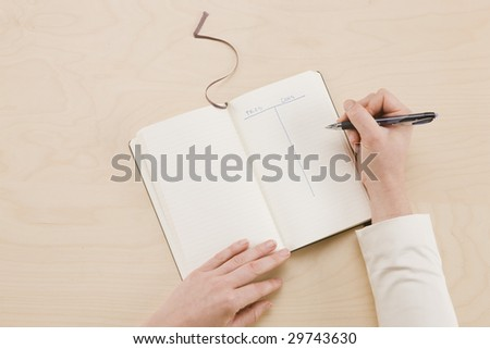 Cons and Pros - notebook sitting on desk with pro's and con's list