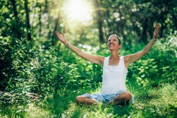 Consciousness opening meditation. Woman empowering the sense of higher consciousness and awareness, sitting on the ground with open arms, surrounded by lush vegetation and natural light