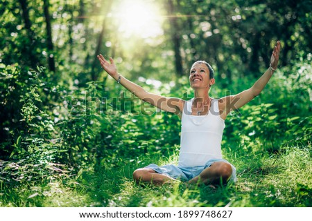 Consciousness opening meditation. Woman empowering the sense of higher consciousness and awareness, sitting on the ground with open arms, surrounded by lush vegetation and natural light Stock photo ©