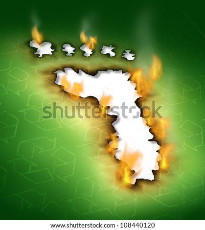 Conservation concept as a footprint hole with smoke damaged burnt green paper edges burning on fire with recycling symbols as an icon of global warming with nature and environmental pollution.