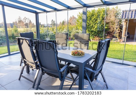 Conservatory of glass with table and chairs in garden Сток-фото ©
