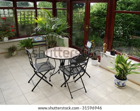 conservatory tables chairs plants room in house next to garden #31596946