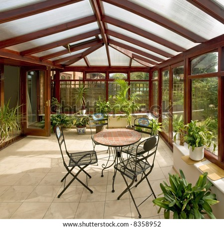 conservatory tables chairs plants room in house next to garden #8358952