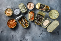 Conserves of canned fish with different types of fish and seafood, opened and closed cans with Saury, mackerel, sprats, sardines, pilchard, squid, tuna, over grey stone surface, top view space for