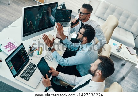 Considering the next step. Top view of young modern men in formalwear analyzing stock market data while working in the office